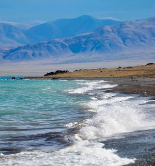 Surfa le onde su un lago di montagna in mongolia