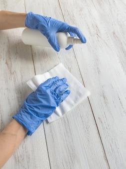 Flacone spray igienizzante antibatterico per la pulizia delle superfici disinfettante contro la diffusione di covid-19 con guanti blu medici