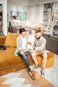 Superficie per divano. dubbioso uomo attento che presenta la propria variante di materiale mentre sua moglie trasporta campioni