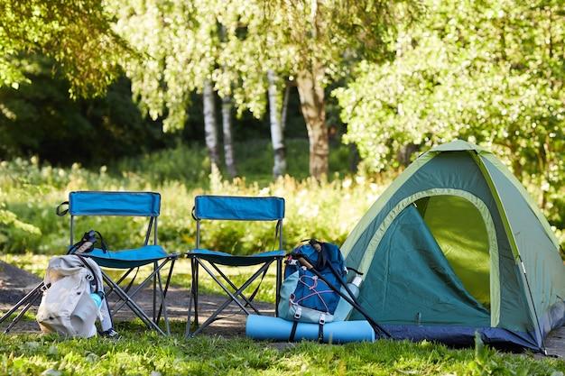 Immagine della superficie della tenda vuota e attrezzatura da campeggio in campeggio nella foresta, copia dello spazio