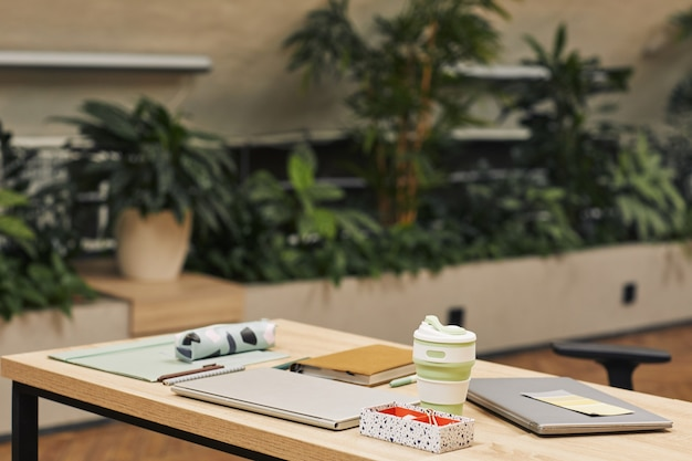 Immagine di superficie della moderna biblioteca universitaria decorata con piante, concentrarsi sul posto di lavoro con lo studio delle forniture in primo piano, copia spazio