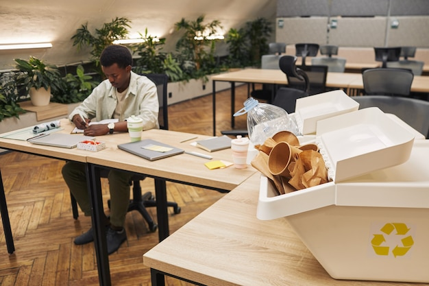 Immagine di superficie di due contenitori per lo smistamento dei rifiuti sulla scrivania all'interno di un ufficio moderno con giovane afro-americano che lavora, copia spazio