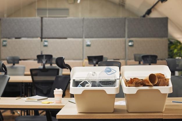 Immagine di superficie di due contenitori per la raccolta differenziata sulla scrivania in ufficio interno, copia dello spazio