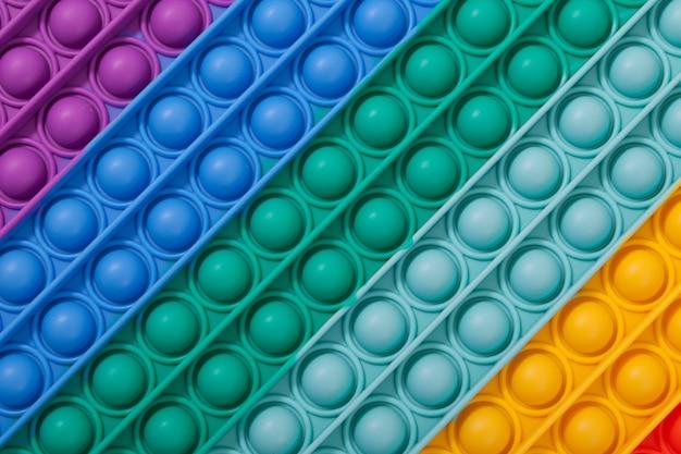 Superficie del giocattolo per bambini in gomma multicolore pop it, primo piano. tocca la bolla, gioco con le dita.
