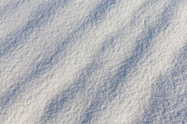 La superficie della neve bianca e bella reale dopo la nevicata. la superficie della neve forma delle ombre nella foto. primo piano in inverno
