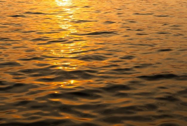 Superficie dell'acqua e delle onde nell'ora del tramonto per il materiale di fondo