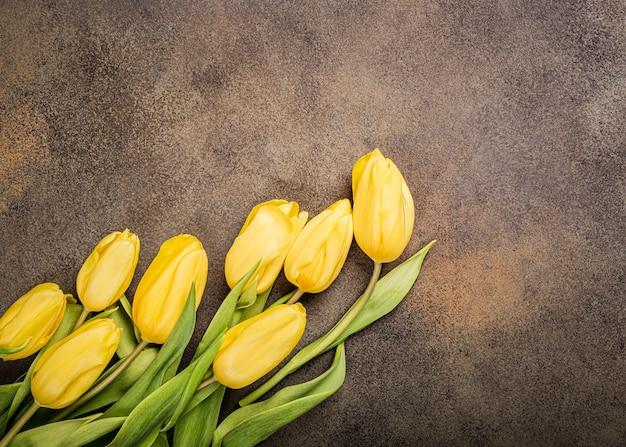 Superficie con tulipani gialli. biglietto di auguri per la festa della mamma. copia spazio