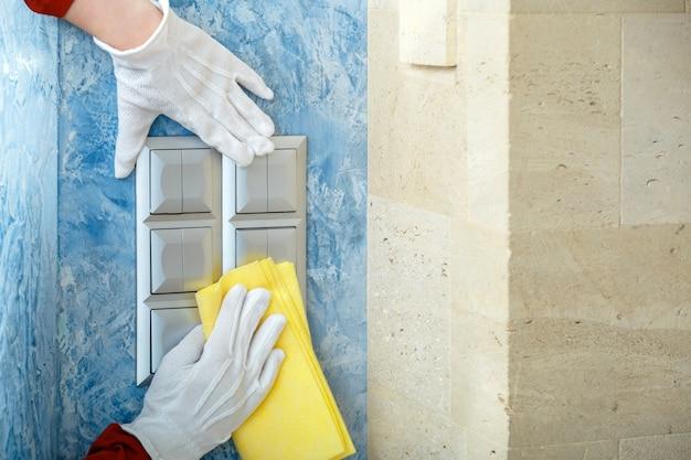Disinfezione delle superfici. il lavoratore domestico in guanti bianchi pulisce gli interruttori della luce con un panno sulla parete con spray alcolico e straccio. nuovo normale servizio di pulizia del coronavirus covid 19 di uffici, negozi, luoghi pubblici.
