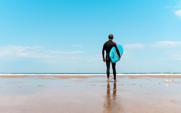 Surfista sulla spiaggia con la tavola in mano che guarda l'orizzonte e si prepara a surfare