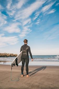 Surfista che entra nell'acqua con la sua tavola da surf.