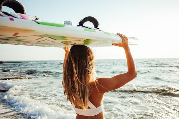 Ragazza del surfista sulla spiaggia al tramonto