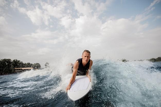 Surfista sdraiato sul bordo bianco e nuotare lungo il fiume