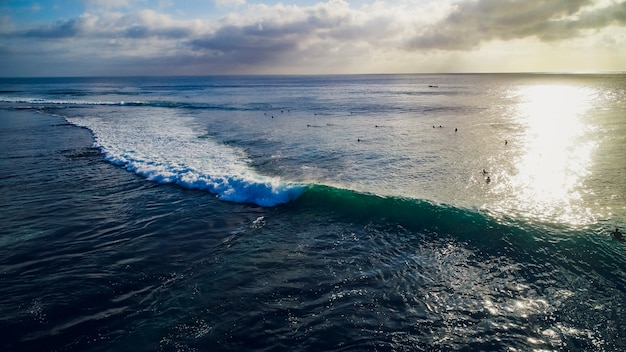 Giro del surfista sulle onde nel tramonto dell'oceano, vista dall'alto