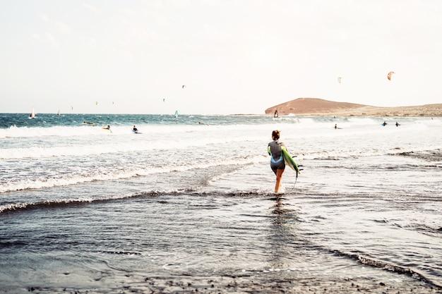 Surfista in piedi sulla spiaggia con tavole da surf preparando a navigare in onde alte