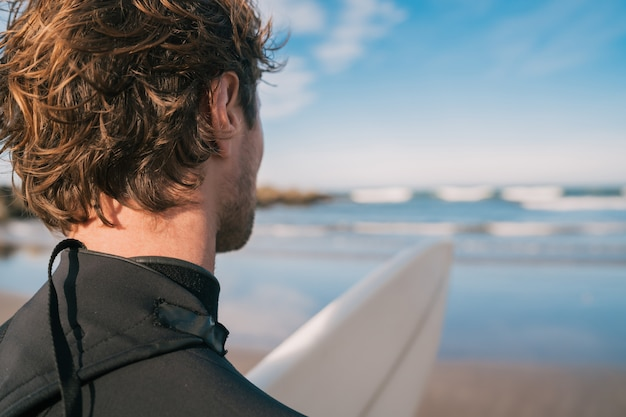 Surfista in piedi sulla spiaggia di sabbia e guardando il mare