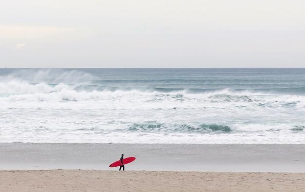 Surfista con un bordo rosso che cammina sulla spiaggia