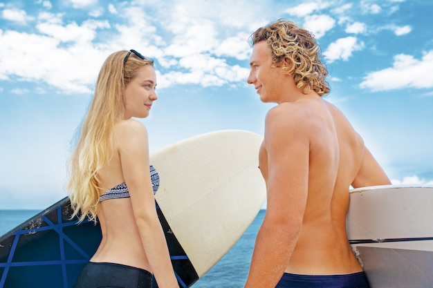 Surfisti in spiaggia- coppia sorridente di surfisti che camminano sulla spiaggia e si divertono in estate. sport estremo e concetto di vacanza