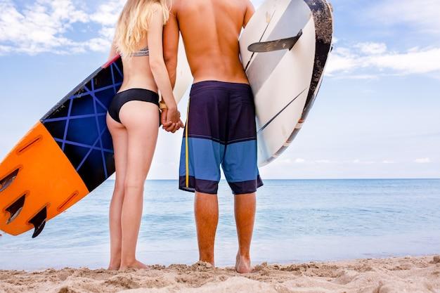 Surfisti in spiaggia- coppia sorridente di surfisti che camminano sulla spiaggia e si divertono in estate