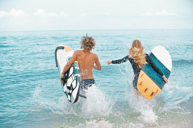 Surfisti in spiaggia sorridente coppia di surfisti che camminano sulla spiaggia e si divertono in estate.