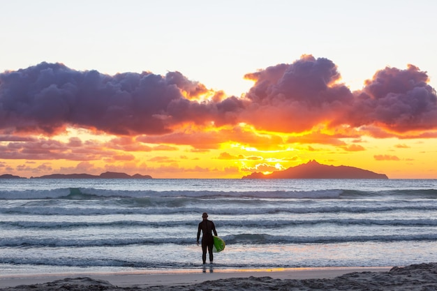 Surfisti sulla spiaggia dell'oceano in nuova zelanda