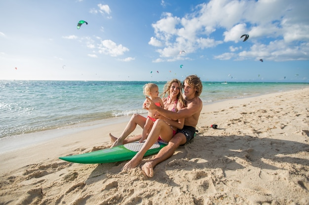 La famiglia felice del surf si siede sul concetto della tavola da surf sullo sport e sul divertimento della famiglia