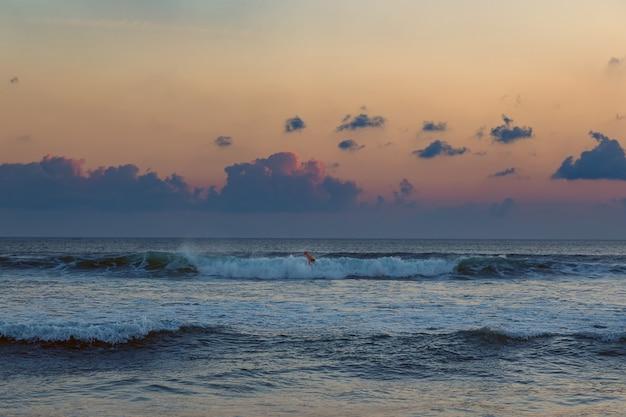 Uomo praticante il surfing al tramonto in seminyak, bali