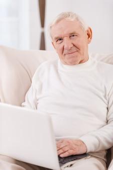 Navigare in rete. fiducioso uomo anziano che lavora al laptop e guarda la telecamera mentre è seduto su una sedia nel suo appartamento