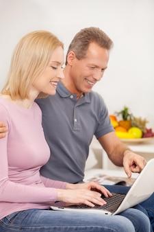 Navigare in rete insieme. vista laterale allegra coppia matura utilizzando laptop insieme e sorridente