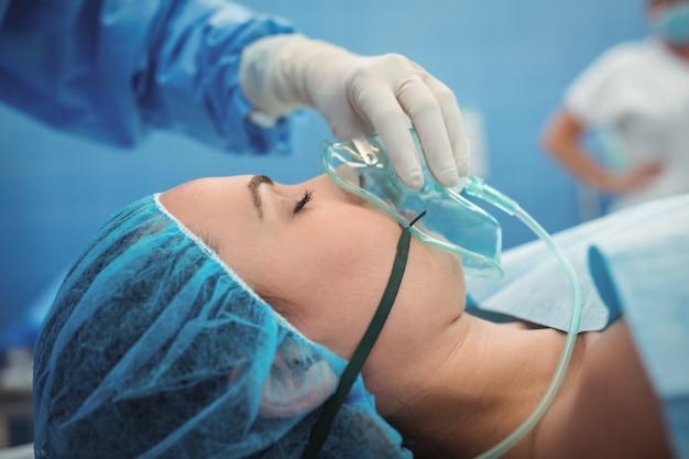 Chirurgo che regola maschera di ossigeno sul teatro in funzione della bocca paziente