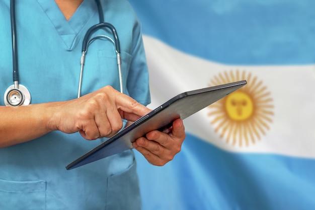 Chirurgo o medico utilizzando una tavoletta digitale sullo sfondo della bandiera dell'argentina