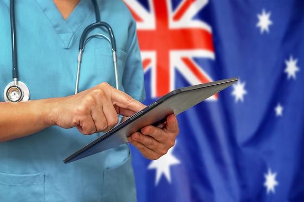 Chirurgo o medico utilizzando una tavoletta digitale sullo sfondo della bandiera dell'australia