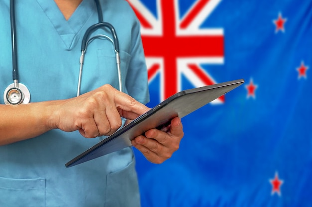 Chirurgo o medico utilizzando una tavoletta digitale sullo sfondo della bandiera della nuova zelanda