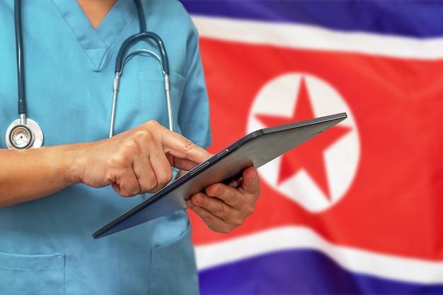 Chirurgo o medico utilizzando una tavoletta digitale sullo sfondo della bandiera della corea del nord