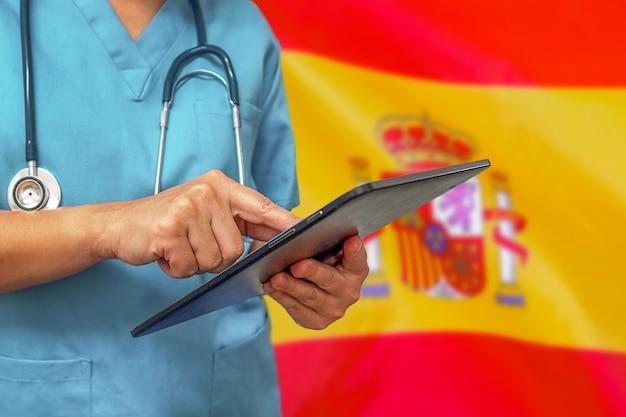 Chirurgo o medico utilizzando una tavoletta digitale sullo sfondo della bandiera della spagna