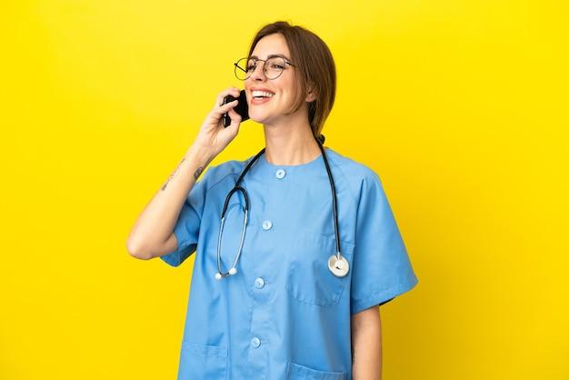 Donna medico chirurgo isolata su sfondo giallo che tiene una conversazione con il telefono cellulare