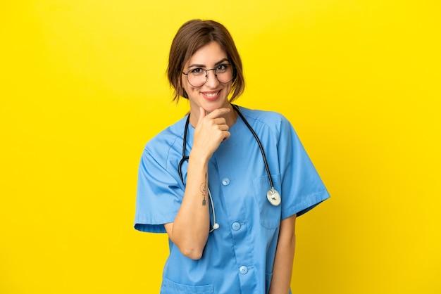 Donna medico chirurgo isolata su sfondo giallo con occhiali e sorridente