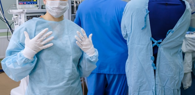 Un chirurgo in maschera medica e guanti sterili in lattice in sala operatoria