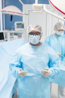 Chirurgo in uniforme protettiva, maschera, guanti e occhiali che ti guardano contro il suo assistente che prepara strumenti medici prima dell'operazione
