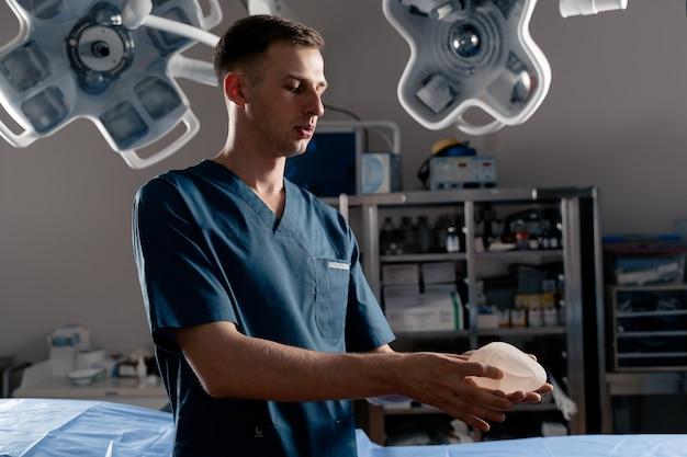 Il chirurgo tocca e stringe le protesi al silicone per il controllo di qualità. aumento del seno e chirurgia del sollevamento