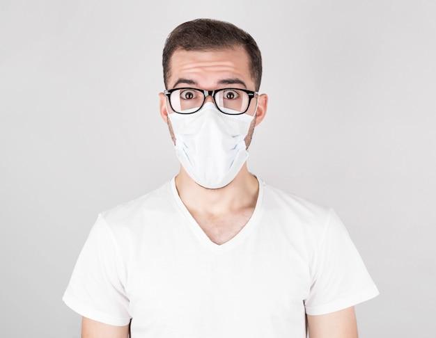 Un chirurgo con una maschera medica bianca e occhiali sta con sorpresa su un muro bianco. dopo aver contratto covid 19, influenza e raffreddori stagionali.