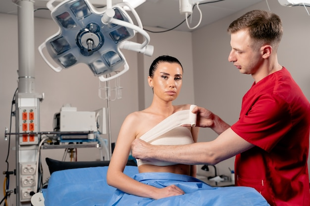 Chirurgo con paziente donna in sala operatoria prima dell'aumento del seno per ragazza. il dottore avvolge il torace del paziente dopo l'aumento del seno