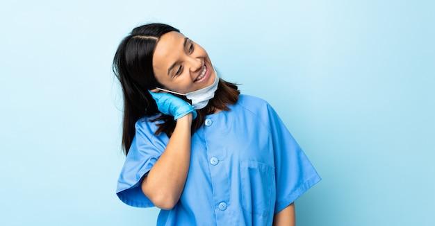 Donna del chirurgo sopra la parete blu che pensa un'idea