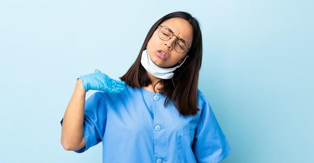 Donna del chirurgo sopra la parete blu con l'espressione stanca e malata