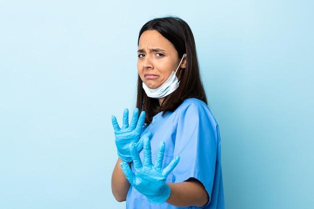 Donna del chirurgo sopra le mani d'allungamento nervose isolate della parete blu alla parte anteriore