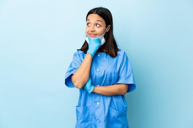 Donna del chirurgo sopra la parete blu isolata che pensa un'idea mentre osservando in su
