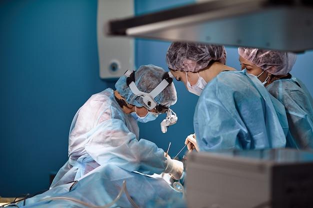 Chirurghi e paramedico in maschera e paziente operante