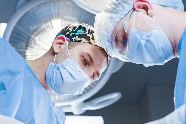 I chirurghi fanno l'operazione di plastica in clinica medica. correzione della forma del viso per il paziente
