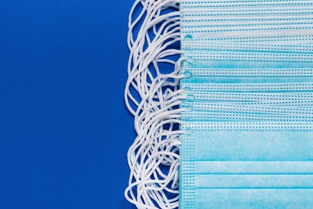 Maschere chirurgiche e mediche per coronaviruse su sfondo di colore blu classico. primo piano del bendaggio facciale usa e getta con cinturini per le orecchie in gomma. copia spazio, mascherine efficaci nella protezione da covid-19