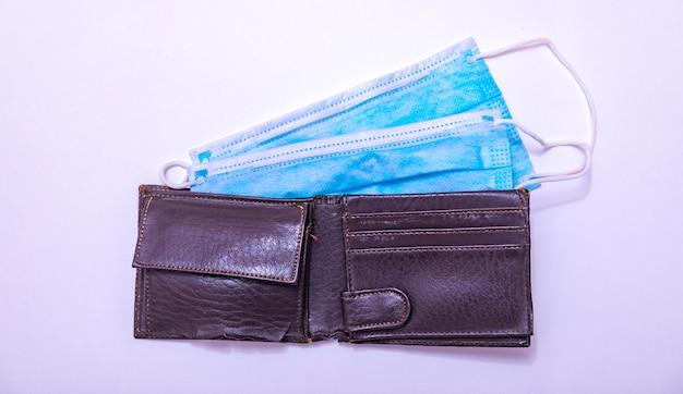 Maschere chirurgiche blu in un portafoglio. l'alto valore delle maschere facciali durante l'epidemia