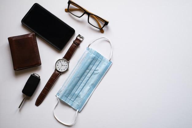 Maschera chirurgica, smartphone, portafoglio, orologio da polso e occhiali su sfondo grigio con spazio per le copie